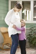 Stock Photo of Expectant mother embracing daughter (4-5)
