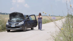 woman with the broken down car on a country road ,call a help - stock footage
