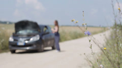 Broken down car on a country road, focus on flower Stock Footage