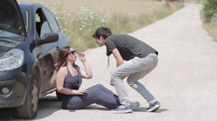 Man helps a woman with her broken down car Stock Footage