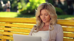 Young female reads message laptop smiles chatting social network, click for HD Stock Footage