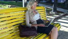 Pretty girl sitting yellow bench typing, social network stedicam, click for HD Stock Footage