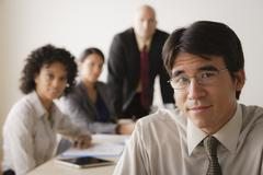 Stock Photo of Young businessman looking at camera, business team in background