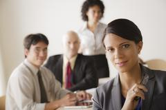 Stock Photo of Young businesswoman looking at camera, business team in background