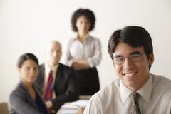Young businessman looking at camera, business team in background - stock photo