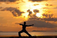 Man silhouette doing yoga exercise archer Stock Photos