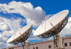 Satellite tv antenna on blue sky and clouds background Stock Photos