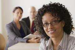 Businesswoman looking at camera, business team in background - stock photo