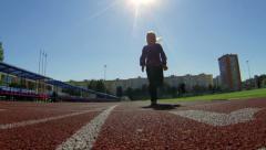 Small girl on stadium line running to camera Stock Footage