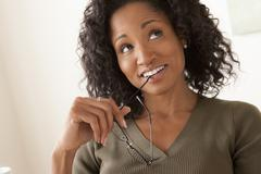 Stock Photo of Portrait of smiling mid adult woman holding glasses