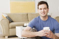 Stock Photo of Portrait of smiling mid adult man holding mug