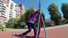 Young child making exercises on sportsground, outdoor Stock Footage