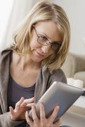Stock Photo of Smiling mid adult woman using digital tablet