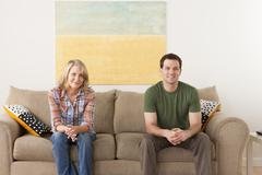 Smiling mid adult couple sitting on sofa - stock photo