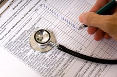 a doctor or nurse completing a patiend questionairre - stock photo
