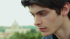 Sad and depressed young man ,have tears in his eyes - saint peter in background Stock Footage