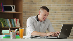 Attractive male student sitting at table and studying with books and laptop - stock footage