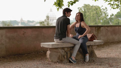 a young man and woman on a bench and talk and laugh - having a fun - stock footage