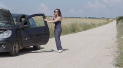 A attractive woman's car breaks down she uses her cell phone to call for help Stock Footage