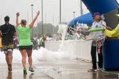 Runners get soaked by squirt guns at race finish line Stock Photos