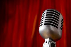 vintage microphone in front of red curtain - stock photo
