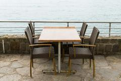 Stock Photo of empty chairs side of sea