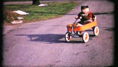 149 - dad gives his son a push in his wagon - vintage film home movie Stock Footage
