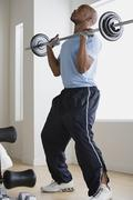 Man lifting barbell in gym Stock Photos