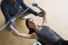 Woman lifting barbell while instructor assisting her Stock Photos