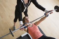 Woman lifting barbell while instructor assisting her - stock photo