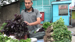 Muslim man selling lettuce in Dushanbe bazaar, market in Central Asia Stock Footage