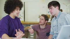Young male students chatting and working together with technology Stock Footage