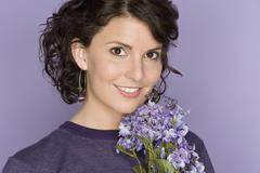Stock Photo of Portrait of happy mid adult woman holding bunch of flowers