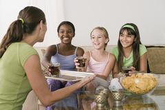 Woman serving drinks for three girls (10-11) at slumber party Stock Photos