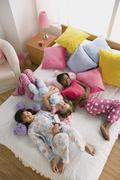 Three girls (10-11) lying on bed at slumber party Stock Photos