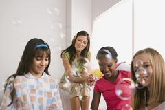 Three girls (10-11) and woman blowing bubbles at slumber party Stock Photos