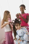 Three girls (10-11) doing hair at slumber party - stock photo