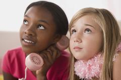 Portrait of two girls (10-11) using phone at slumber party Stock Photos