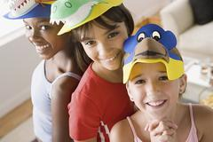 Portrait of three girls (10-11) wearing funny hats at slumber party Stock Photos