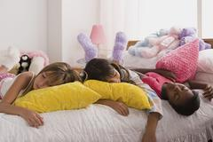 Three girls (10-11) sleeping on bed at slumber party Stock Photos
