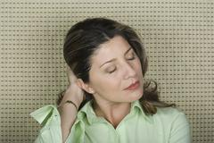 Stock Photo of Studio portrait of senior woman with hand in hair