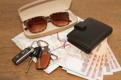 Avaimet ja aurinkolasit tiekartan taskurahaa, valmis matkustamaan Kuvituskuvat