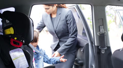 Working Mother Puts Child into Safety Seat Stock Footage