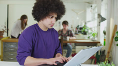 Young male student concentrating as he works within a shared study space - stock footage
