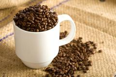 Whole coffee beans in cup Stock Photos