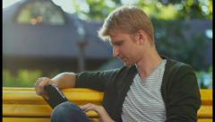 Young blond male reading tablet pc electronic book in park, click for HD Stock Footage