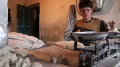 Young man weighing dough for bread in Tajik bakery Stock Footage