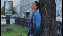 Young adult with headache in park, problem, pain, relationships, click for HD - stock footage