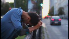 Young adult depression, heart break standing fence traffic cars, click for HD Stock Footage