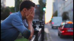 Headache depression by young male with moving traffic background, click for HD Stock Footage